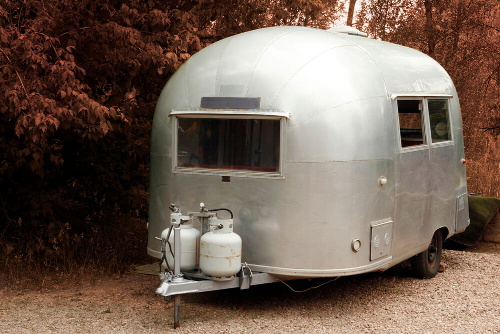 small rv with two propane tanks and regulators